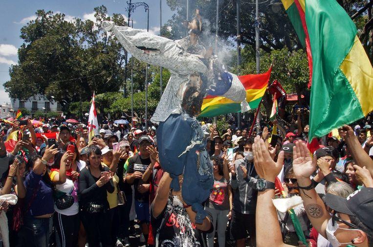 Tegenstanders van Morales verbranden poppen op straat.