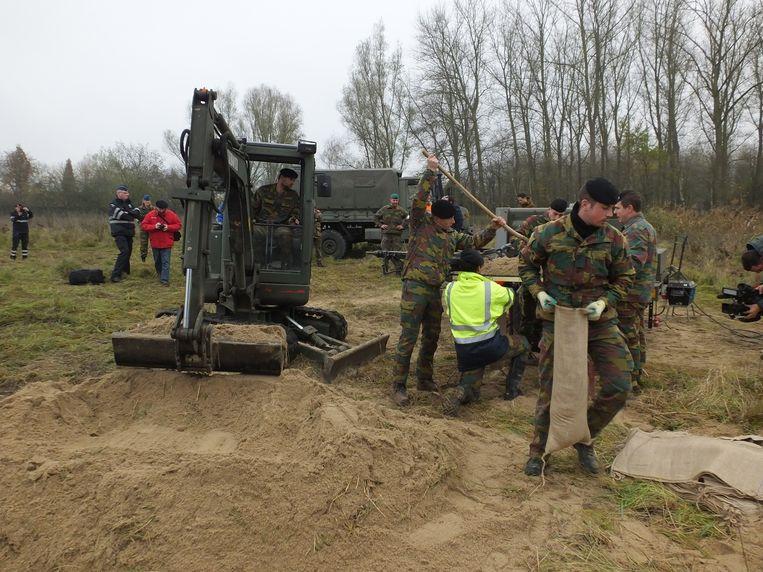Enkele militairen vullen zandzakken om een dam te kunnen bouwen in de oude Leiearm in Astene.