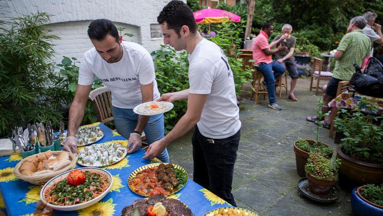 Nashed (blauwe broek) en Nashef zetten de gerechten klaar Beeld Rink Hof