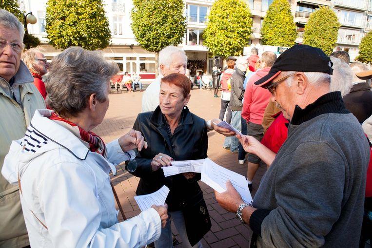 Tweede verblijvers Albert en Claudine delen pamfletten uit.