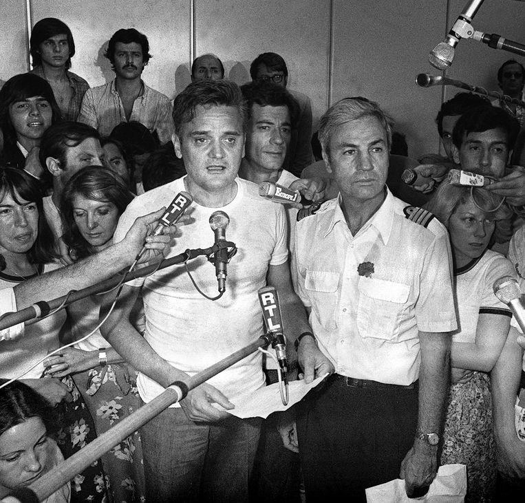 Een foto van 5 juli 1976: Michel Bacos (rechts) en een van de gijzelaars spreken de pers toe.