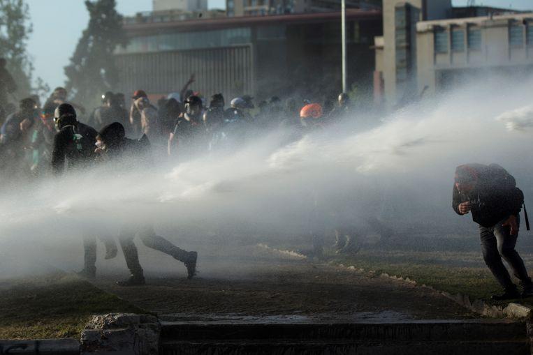 Ook tijdens het referendum raakten tientallen demonstranten in de Chileense hoofdstad Santiago nog slaags met de politie.  Beeld EPA