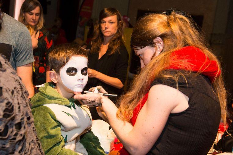 Een jongetje laat zich schminken in de grimestand.