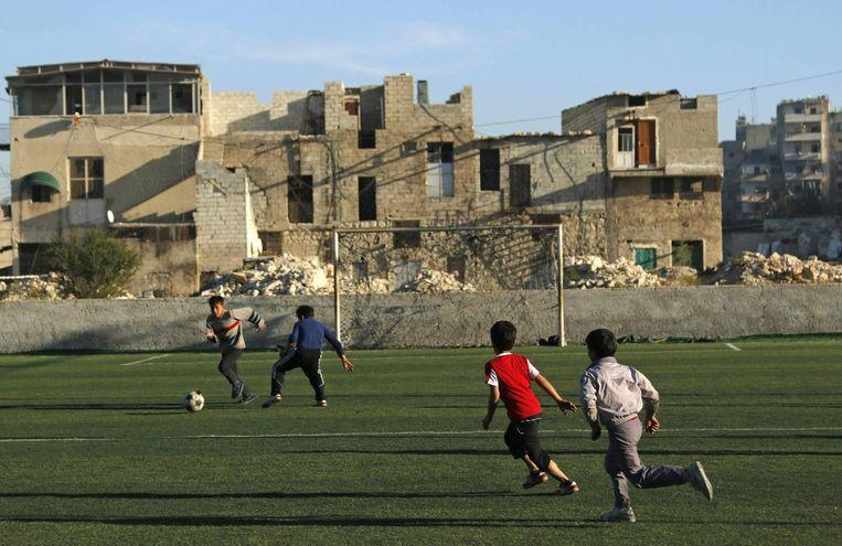 Jongens voetballen in al-Klaseh, een van de belegerde wijken van Aleppo. Beeld reuters