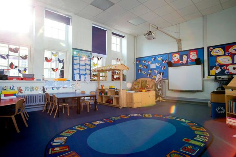 Landscape image of an empty, nursery classroom. there is a rug in the middle of the room.