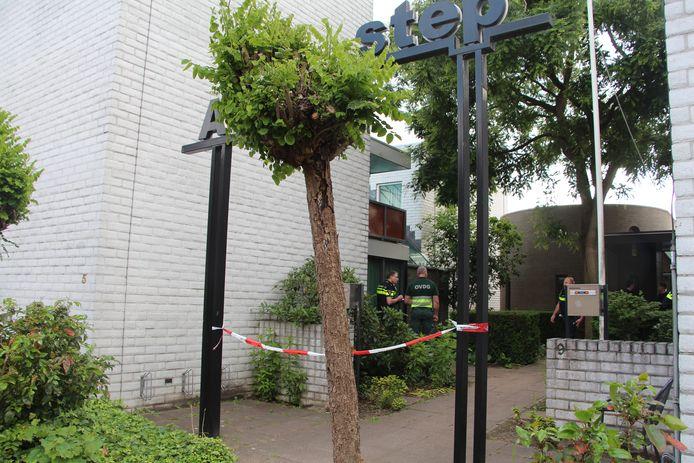 De entree van het complex is afgezet met politielint. Politiemensen en de OVDG van de ambulancedienst overleggen.