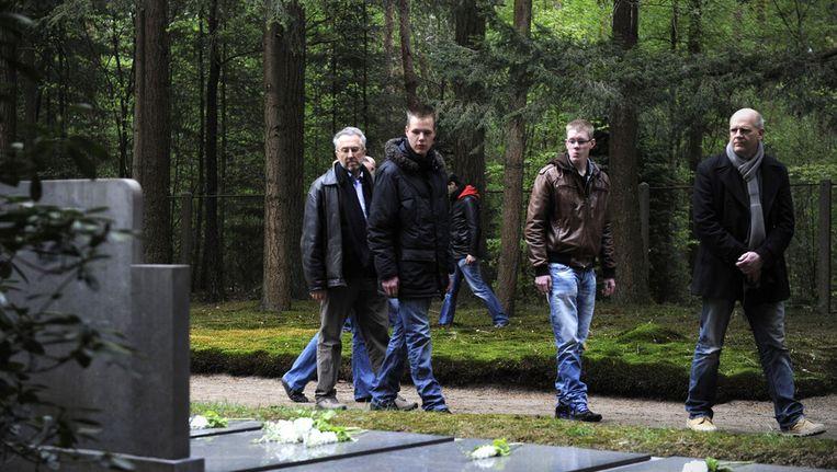 Inwoners van Vorden liepen na afloop van de Nationale Dodenherdenking in 2012 op de algemene begraafplaats langs de Duitse oorlogsgraven. Beeld anp