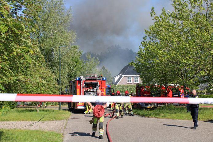 Grijze wolken zijn van verre te zien door een grote brand in een loods in Lelystad.