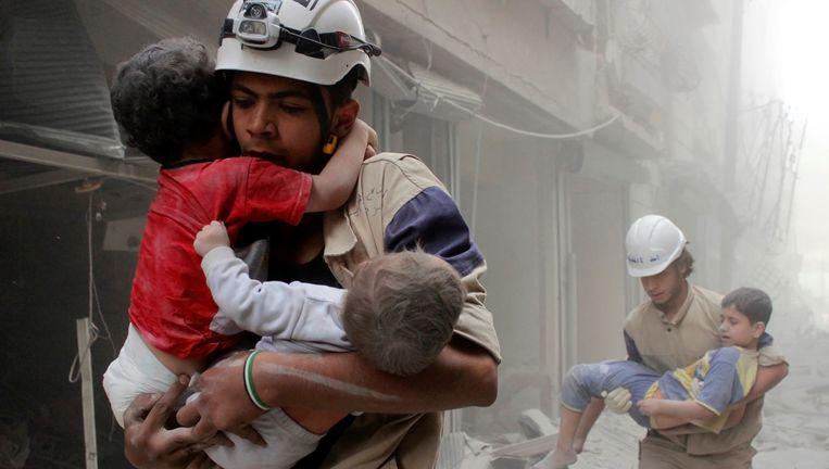 Leden van de hulporganisatie White Helmets redden kinderen in Aleppo. Beeld reuters