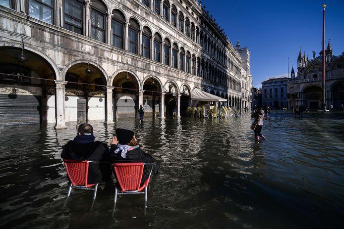 Twee mensen op terrasstoelen in het centrum van Venetië, dat is getroffen door de zwaarste overstroming in 50 jaar.