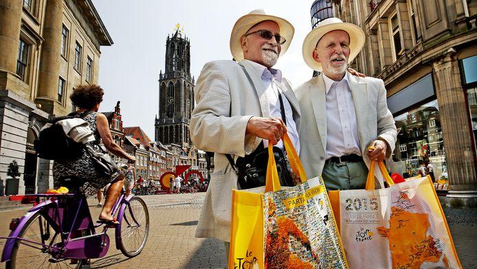 Twee Tour-liefhebers op leeftijd poseren in stijl met zonnehoed bij de Domtoren.