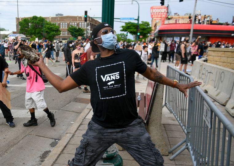 Een demonstrant gooit een steen tijdens een confrontatie met agenten bij een politiebureau in Minneapolis. Beeld EPA