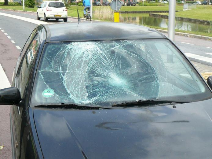 De voorruit van de auto raakte beschadigd, nadat de fietser op het voertuig terecht kwam.