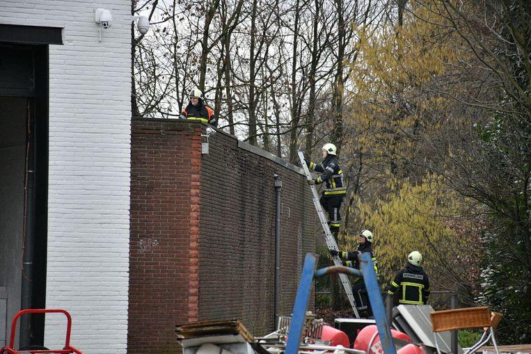 Brandweermannen klimmen over de muur.