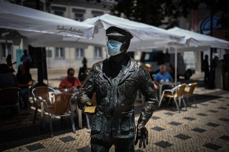 Een standbeeld met een mondmaskertje op in Lissabon.