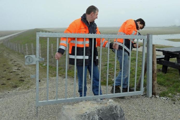 Waterschapsmedewerkers Benny van Gassen (links) en Peter van Dixhoorn plaatsen de hekken terug op de dijk bij Ossenisse, na de uitspraak die de Raad van State daar op verzoek van de Vogelbescherming over deed. archieffoto Peter Nicolai