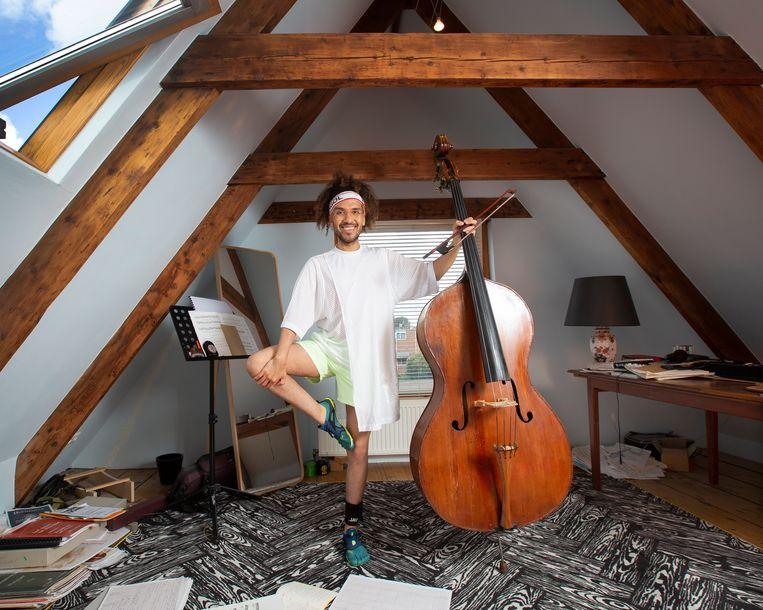 James Oesi op zijn zolder in zijn sportkleding met zijn contrabas. Hij sportte een half jaar volgens een strak sportschema om zijn muziek-prestatie te verbeteren. Beeld Maartje Geels