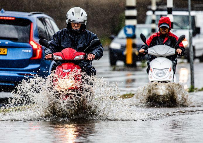 Een wolkbreuk in Dordrecht zorgt telkens voor veel wateroverlast. Mensen banen zich een weg door de plassen.