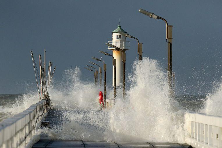 Het zeewater spat over het oosterstaketsel in Nieuwpoort.