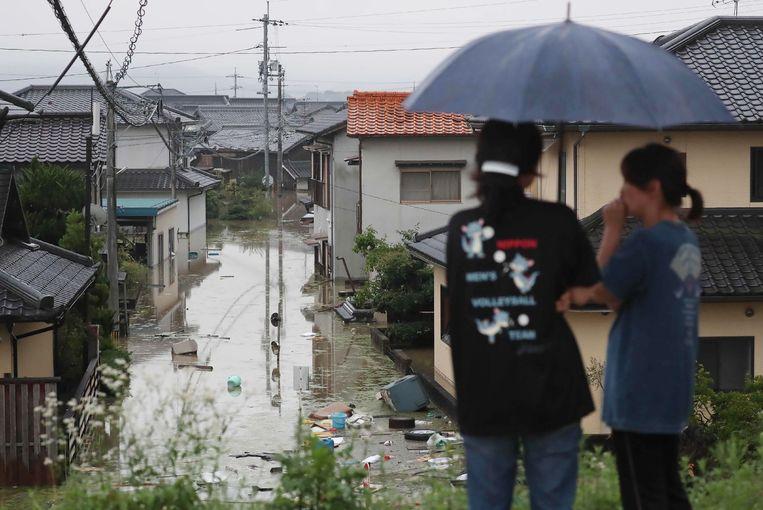 Bewoners kijken naar een overstroomde straat in Kurashiki, Okayama.  Beeld null