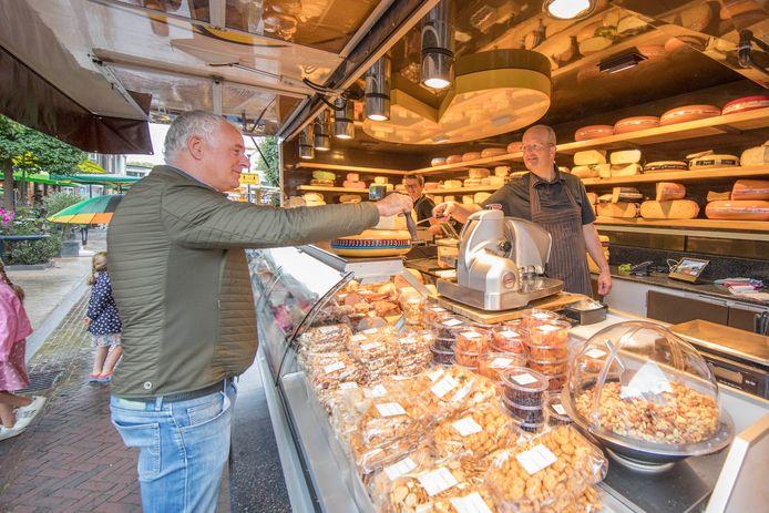 Marktkoopman Cor (r) geeft Hans Zoeteweij een stukje kaas om te proeven.