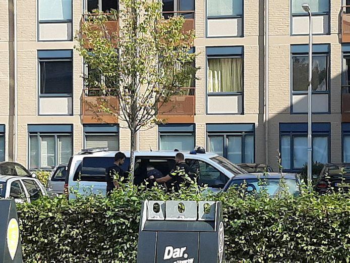 Een verdachte wordt afgevoerd door agenten in zware vesten in Horstacker Nijmegen.