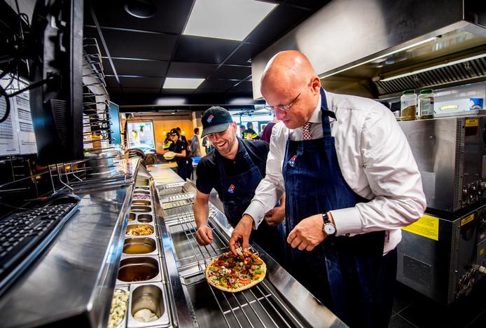 Minister Ferd Grapperhaus bakte vandaag tijdens zijn bezoek nog een pizza bij de Domino's in Zevenkamp.