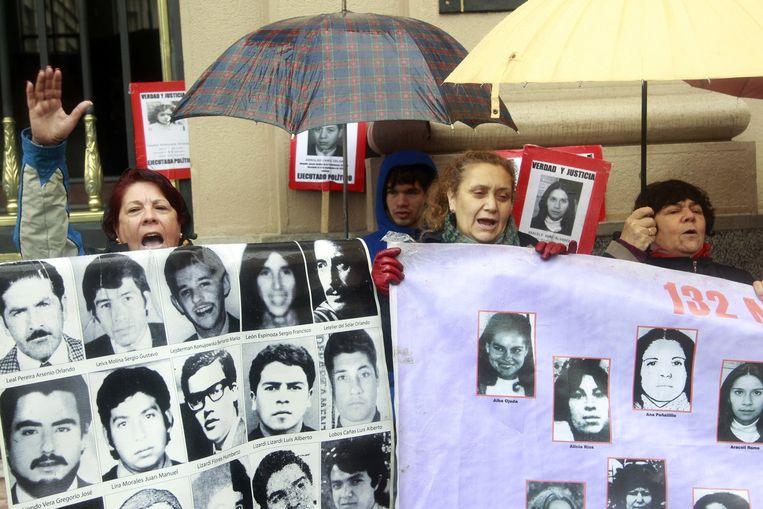 Leden van de vereniging van familieleden van verdwenen en vermoorde slachtoffers van de dictatuur houden zaterdag een manifestatie na het overlijden vrijdag van Manuel Contreras, die leiding gaf aan de moorden op linkse activisten. Beeld afp