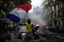 Een 'geel hesje' zwaait met de Franse vlag tijdens rellen in Parijs.