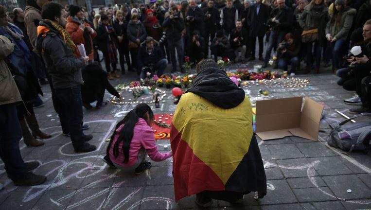 Een man met een Belgische vlag omgeslagen steekt een kaarsje aan op het Beursplein in Brussel. Op het plein zijn mensen dinsdagavond bijeengekomen om de slachtoffers van de aanslagen te herdenken. Beeld afp