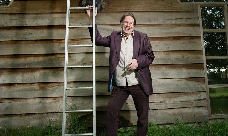 Robbert van Duin voor zijn kantoor van gerecycled materiaal, het hout is afkomstig van oude meerpalen uit het IJsselmeer. Beeld Maartje Geels