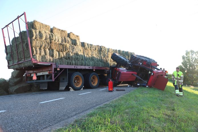 De bestuurder van de trekker raakte gewond toen zijn voertuig omsloeg. De Waalbandijk in Dodewaard ligt bezaaid met hooibalen.