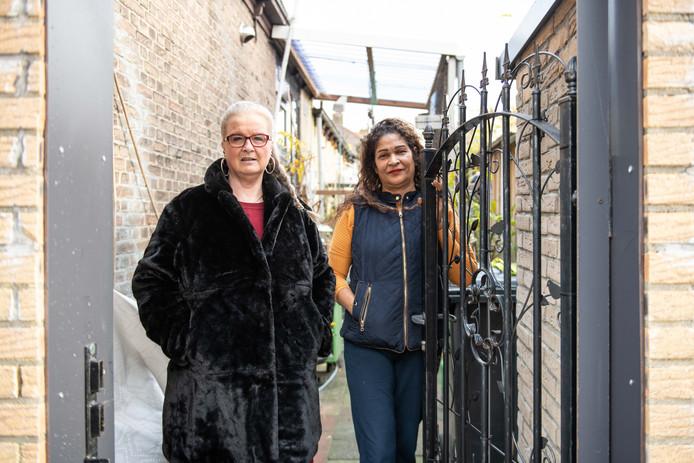 Fenny Hemmers (links) en Cleemy Cerpentier bij de omstreden poort. Ze hebben een al jaren slepende ruzie met eigenaar Jan Brinkers van de naastgelegen kinderopvang Onder de Perenboom.