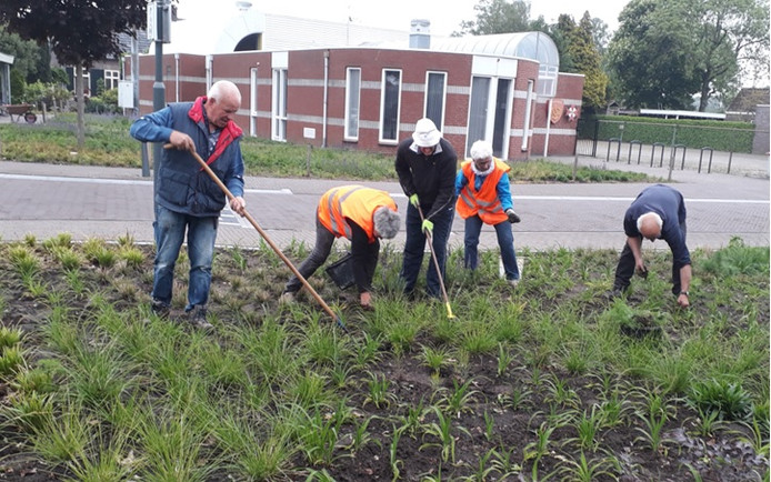 Enkele vrijwilligers waaronder Joop Dielissen (links) leggen de laatste hand aan de vernieuwde dorpskern.