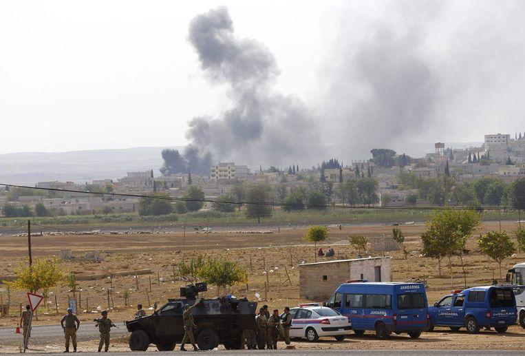 Turkse soldaten houden de wacht bij een grenspost nabij Kobani, waar zwarte rookpluimen opstijgen na aanvallen door IS. Beeld reuters
