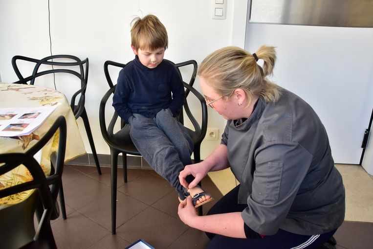 Slagersvrouw Lieselot Devos uit Rollegem-Kapelle probeert een paar nieuwe sandaaltjes aan de voetjes van haar zoontje Remi.