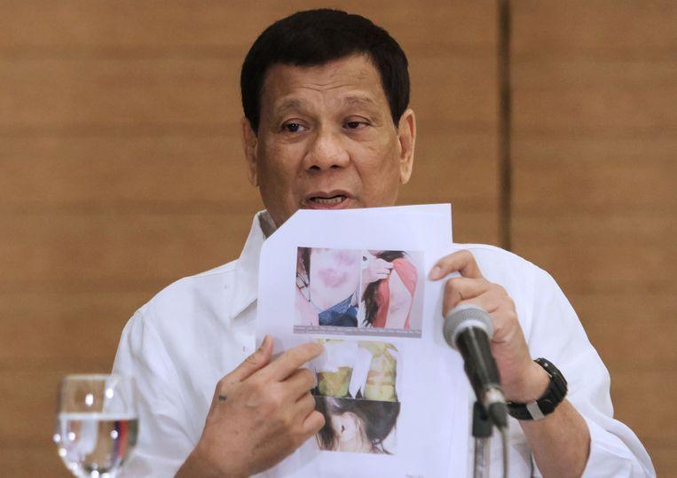 President Rodrigo Duterte van de Filippijnen toont een foto van een Filippijnse arbeidsmigrant die werd mishandeld in Kuwait. Beeld AFP