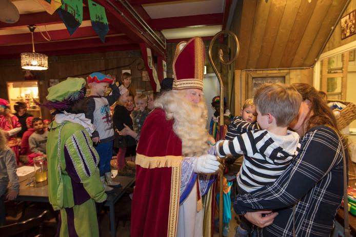 Sinterklaas geeft een kleine bezoeker een hand in het Sinterklaashof in Nuenen.