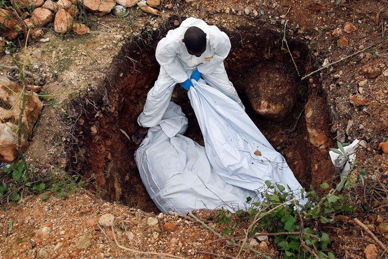 Slachtoffers van de orkaan Matthew op Haïti worden begraven. Beeld REUTERS