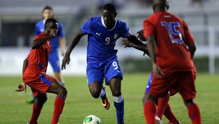 Mario Balotelli worstelt zich door de verdediging van Haïti. Beeld epa