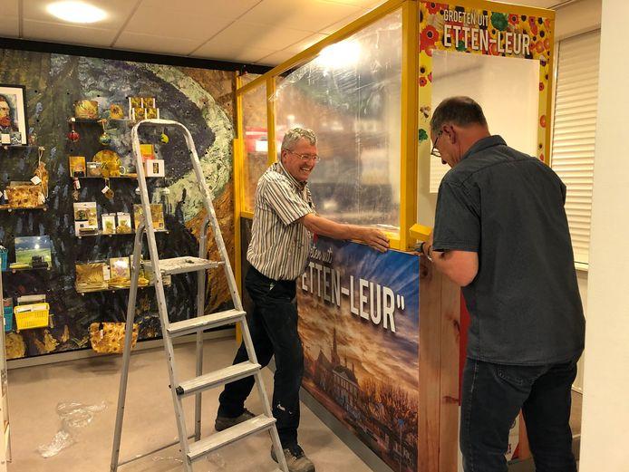 Vrijwilligers Lex Besselink en Huub van Haperen monteren een degelijk op maat gemaakt 'spatscherm' voor de balie van het Toeristisch Informatiepunt op de Markt 4,  dat op 1 juni de deuren weer (beperkt) opent om inwoners en bezoekers de weg te wijzen in Etten-Leur.