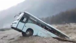 Toeristenbus verdwijnt in kolkende rivier