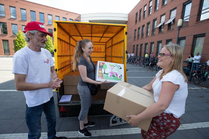 Ruud van de Kerkhof van de Kamper stichting Be Part en Stephanie van Buuren van de Stichting Kansarme Kinderen Nederland geven het eerste pakket aan Patricia Klaus.