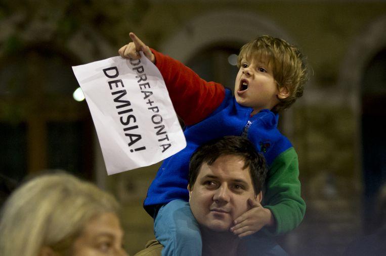 Een kind met een vel papier met de tekst 'Oprea + Ponta - aftreden!' Beeld ap