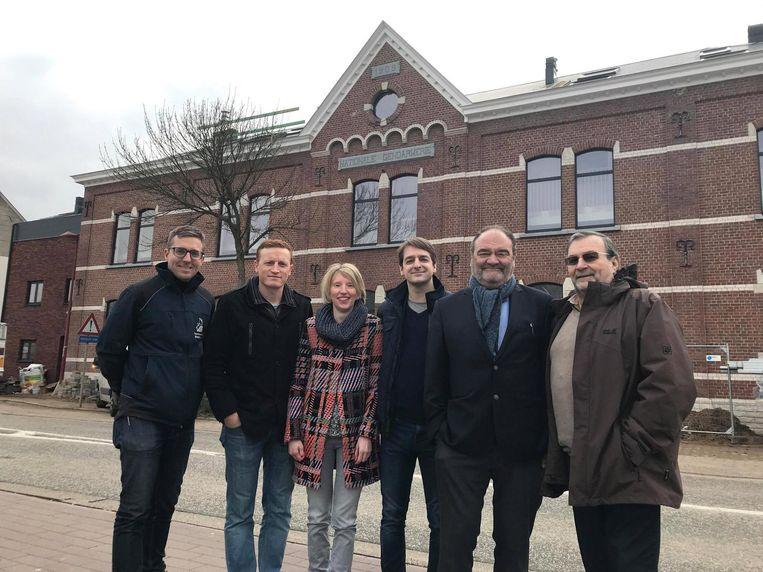 Onder andere Gunther Janssens (schepen van Wonen en Stedenbouw, 3de van rechts) en Guido Claes, voorzitter van Volkswoningbouw (helemaal rechts), poseren voor de gerenoveerde kazerne.
