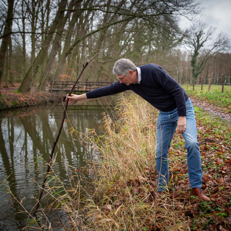 Dijkgraaf Hein Pieper van Waterschap Rijn en IJssel peilt het water in de Baakse Beek.