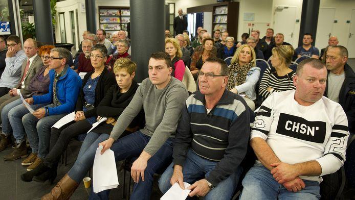 Gemeentebewoners volgen de bijeenkomst van de gemeenteraad waar een beslissing wordt genomen over de opvang van vluchtelingen. Eerder verliep een vergadering over hun komst tumultueus.
