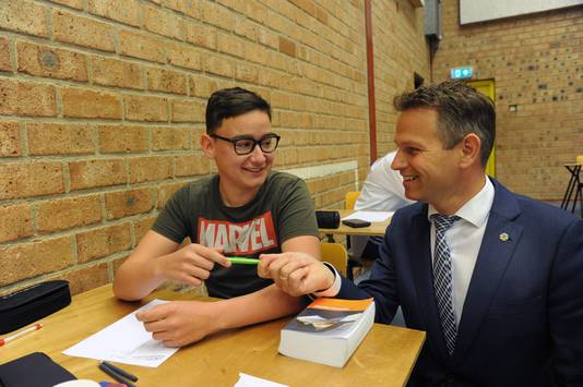 Gedeputeerde Jo-Annes de Bat geeft een pen aan CSW-leerling Joël Geelhoed uit Kamperland.