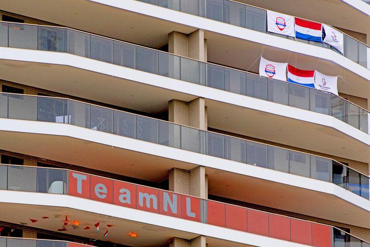 De Nederlandse vlaggen hangen aan het balkon van de Nederlandse Olympiërs in het Olympisch dorp. Beeld anp