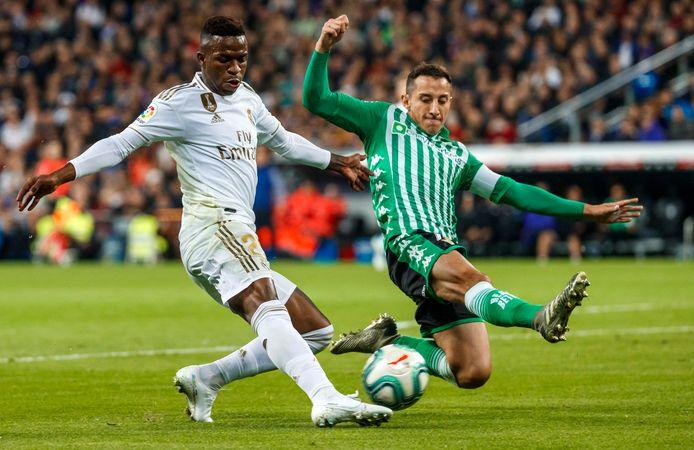Real Betis-aanvoerder Andrés Guardado probeert een voorzet van Real Madrid-aanvaller Vinicius Junior te blokkeren.